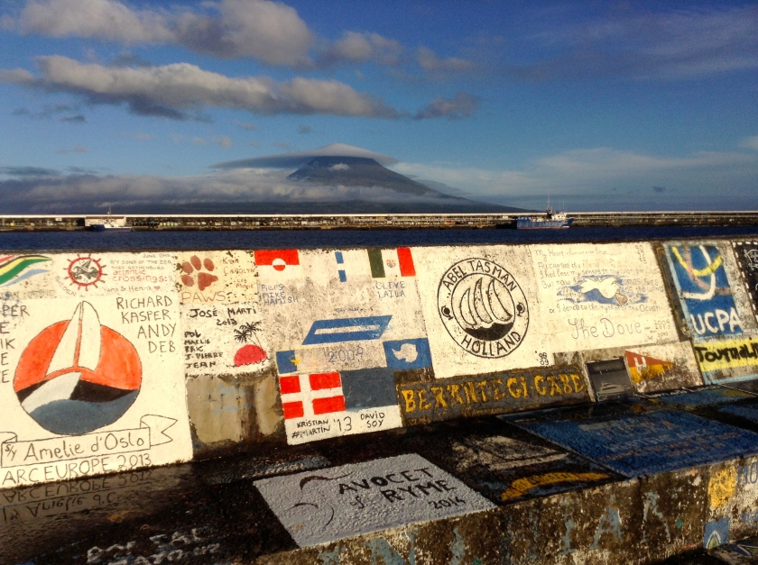 Graffiti covered breakwater at Horta Marina. In the background is Mt. Pico on neighbouring Pico Island capped with an unusual lenticular cloud.